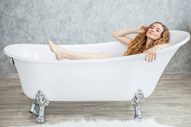 Beautiful young woman relaxing lying in the retro bathtube in the bathroom stock photo