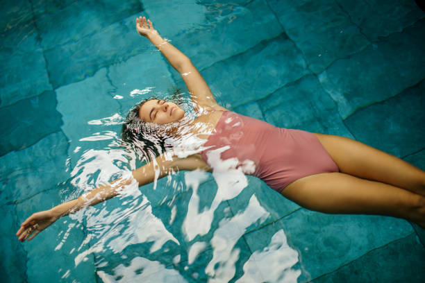 Beautiful young woman relaxing on indoors poolside stock photo