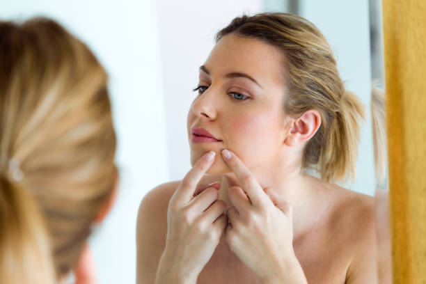 Beautiful young woman removing pimple from her face in a bathroom home. stock photo