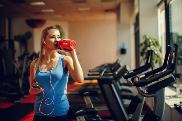 Beautiful young woman resting and drinking water in the gym stock photo