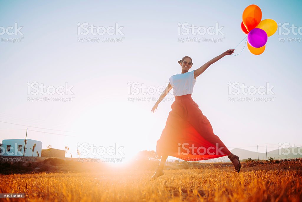 beautiful young woman running in the field with balloons stock photo
