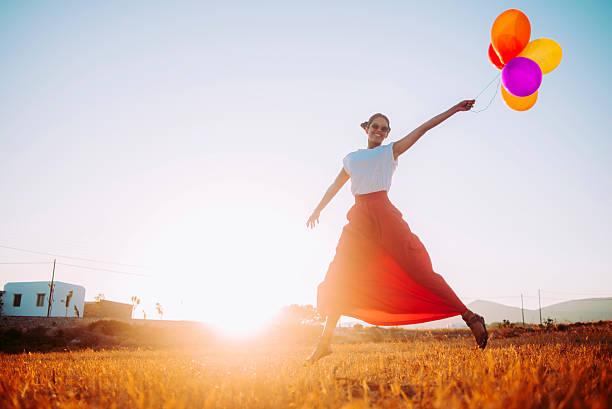 beautiful young woman running in the field with balloons beautiful cheerful young woman running in the field with balloons,nice warm light and sunbeam sun shining through dresses stock pictures, royalty-free photos & images
