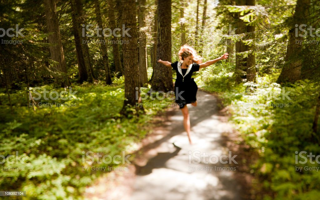 Beautiful young woman running in the woods and appreciating nature royalty-free stock photo