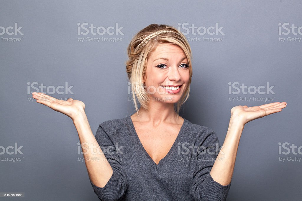 beautiful young woman showing something equal on both empty hands stock photo