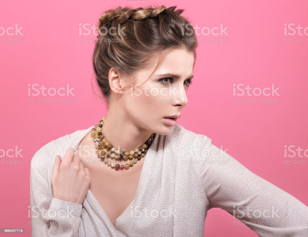 Beautiful young woman shows beads on his neck. airstyle and makeup and a bright blouse stock photo