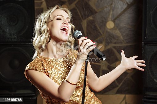 Beautiful young woman singing with the microphone