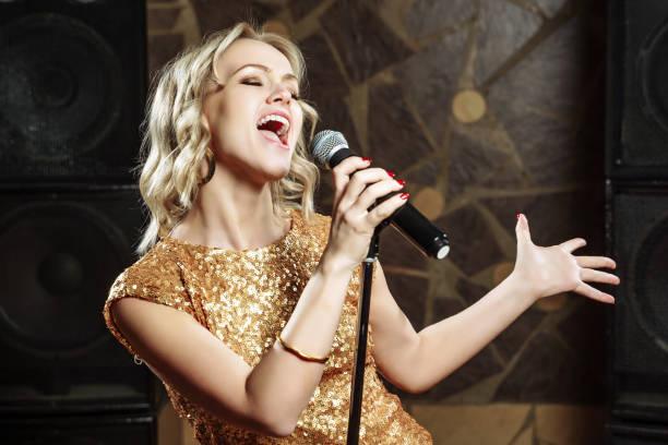 belle jeune femme chantant avec le microphone - chanteuse photos et images de collection