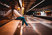 Beautiful young woman sited waiting for the train on a subway station with copy space