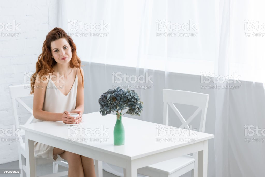 beautiful young woman sitting at table with cup of coffee and flowers in vase at home stock photo