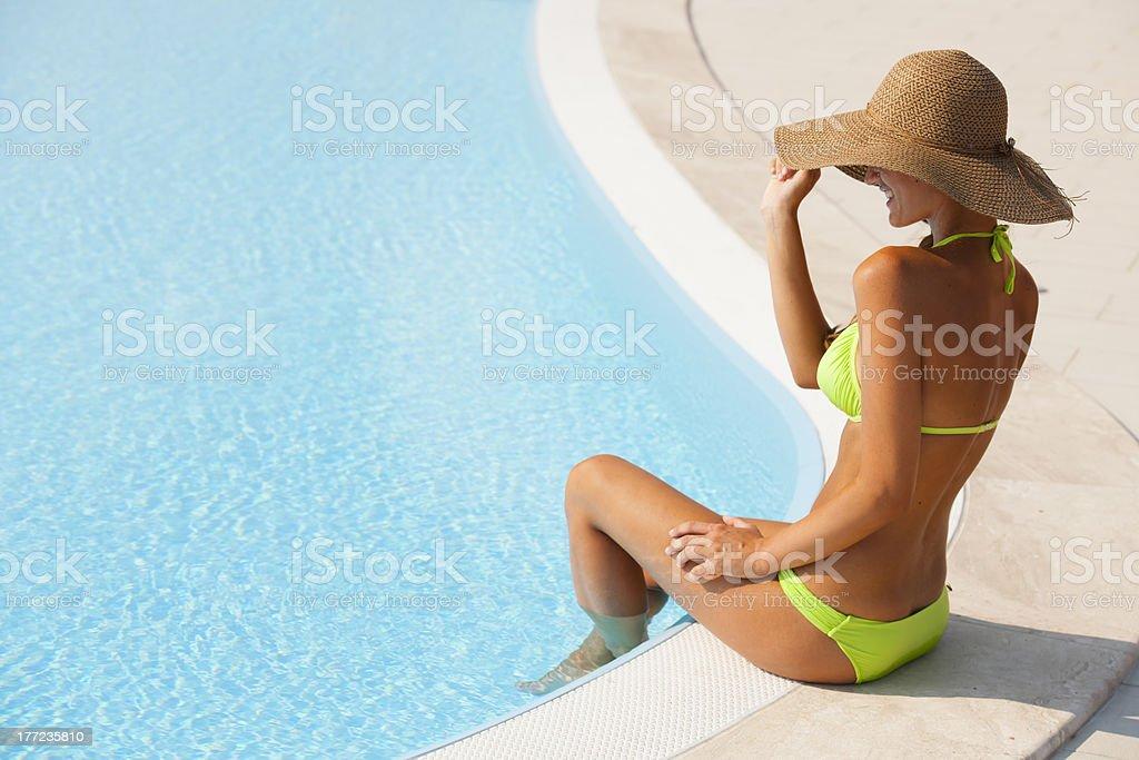 Beautiful Young Woman Sitting By Swimming-pool stock photo