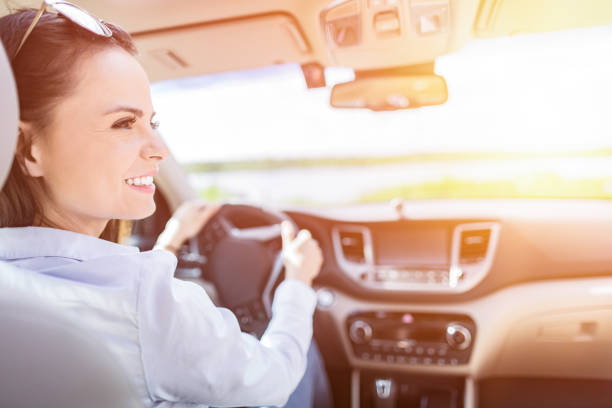 Beautiful young woman sitting in the interior of a new car with a smile. stock photo