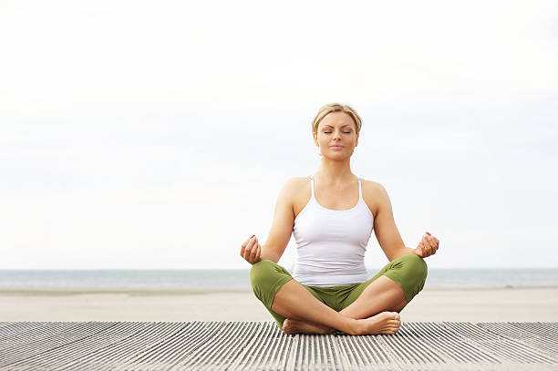 Beautiful young woman sitting in yoga lotus pose at beach Portrait of a beautiful young woman sitting in yoga lotus pose at the beach lotus position stock pictures, royalty-free photos & images