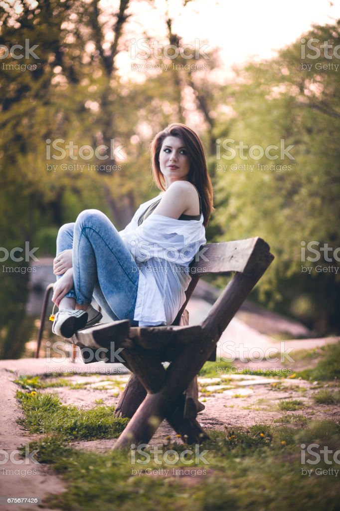 Beautiful young woman sitting on a bench royalty-free stock photo
