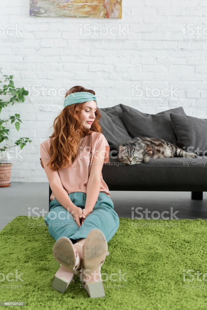 beautiful young woman sitting on floor near her tabby cat at home stock photo