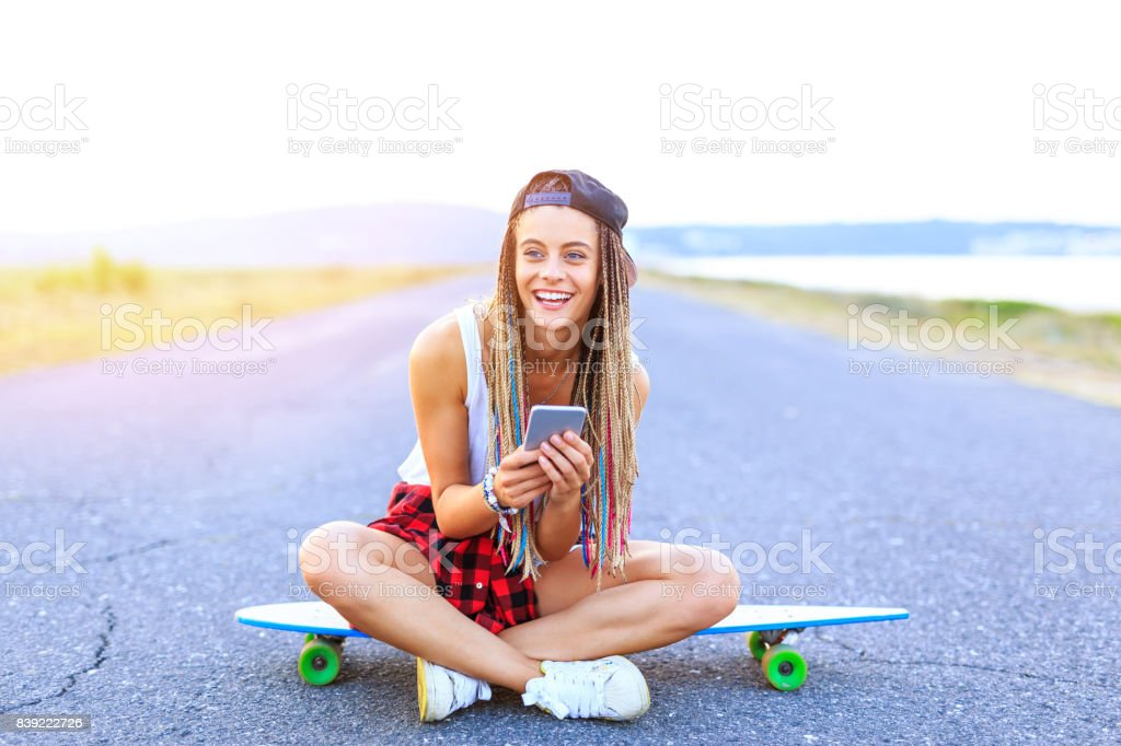 Beautiful young woman sitting on skateboard on road stock photo