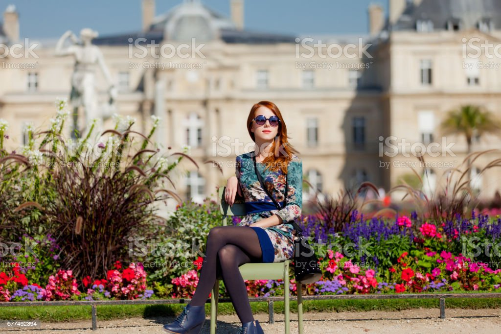 beautiful young woman sitting on the chair near flowerbed on the mansion background – Foto