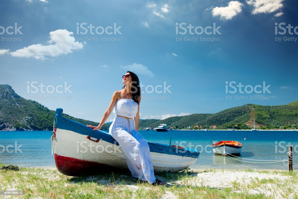 beautiful young woman sitting on the wonderful boat on the coast in Greece stock photo