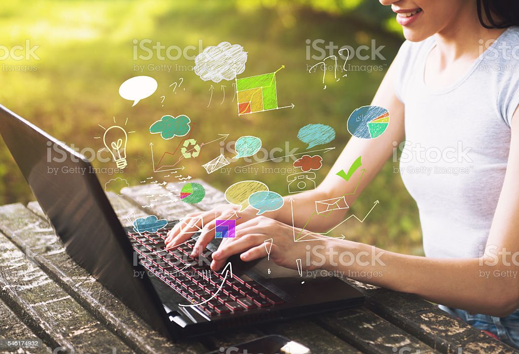 Beautiful young woman sitting outdoors, using a laptop royalty-free stock photo