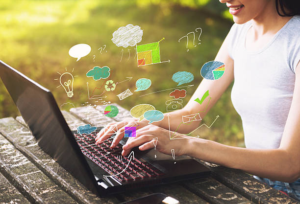 Beautiful young woman sitting outdoors, using a laptop stock photo