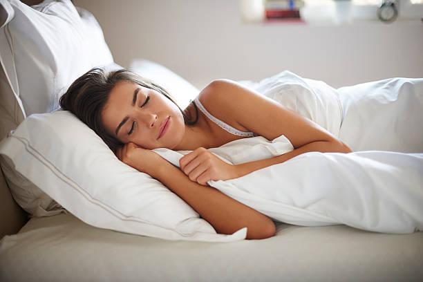 Linda jovem a dormir na cama - foto de acervo