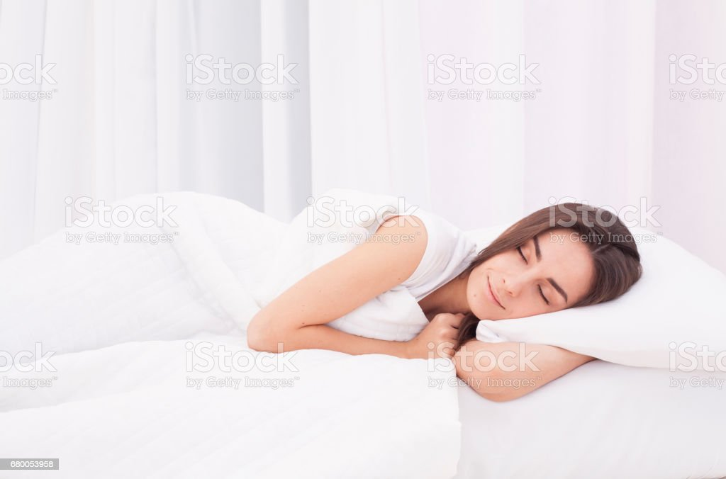 Beautiful young woman sleeping in white bed stock photo
