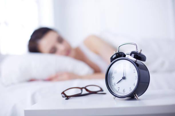Schöne junge Frau schlafen beim liegen im Bett bequem und selig auf dem Hintergrund der Wecker – Foto
