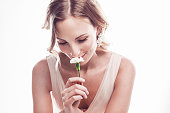 Beautiful young woman smelling  a flower with a look of love on her face.