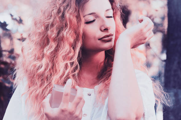 Beautiful young woman smelling the scent of a perfume stock photo