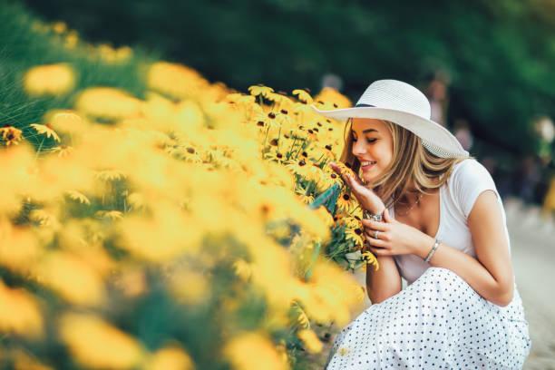 vacker ung kvinna som luktar gul blomma i parken. - summer smell bildbanksfoton och bilder
