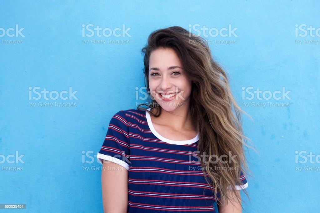 belle jeune femme souriant sur fond bleu - Photo