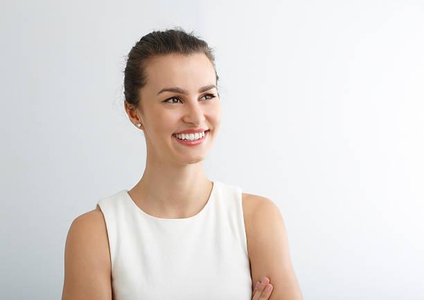 Cтоковое фото Красивая молодая женщина, улыбающаяся на белом фоне.