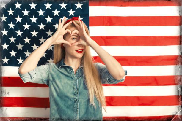 schöne junge frau lächelnd und gestikulierend vor dem hintergrund der amerikanischen flagge am unabhängigkeitstag - schöne englische wörter stock-fotos und bilder