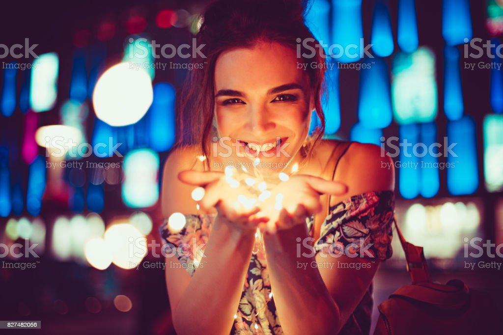 Mulher jovem e bonita sorrindo e conversando guirlandas de luzes na cidade - foto de acervo