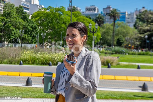 Beautiful young woman smiling and talking on the cell phone, holding a cup of coffee in her left hand in a public park at Buenos Aires, Argentina.