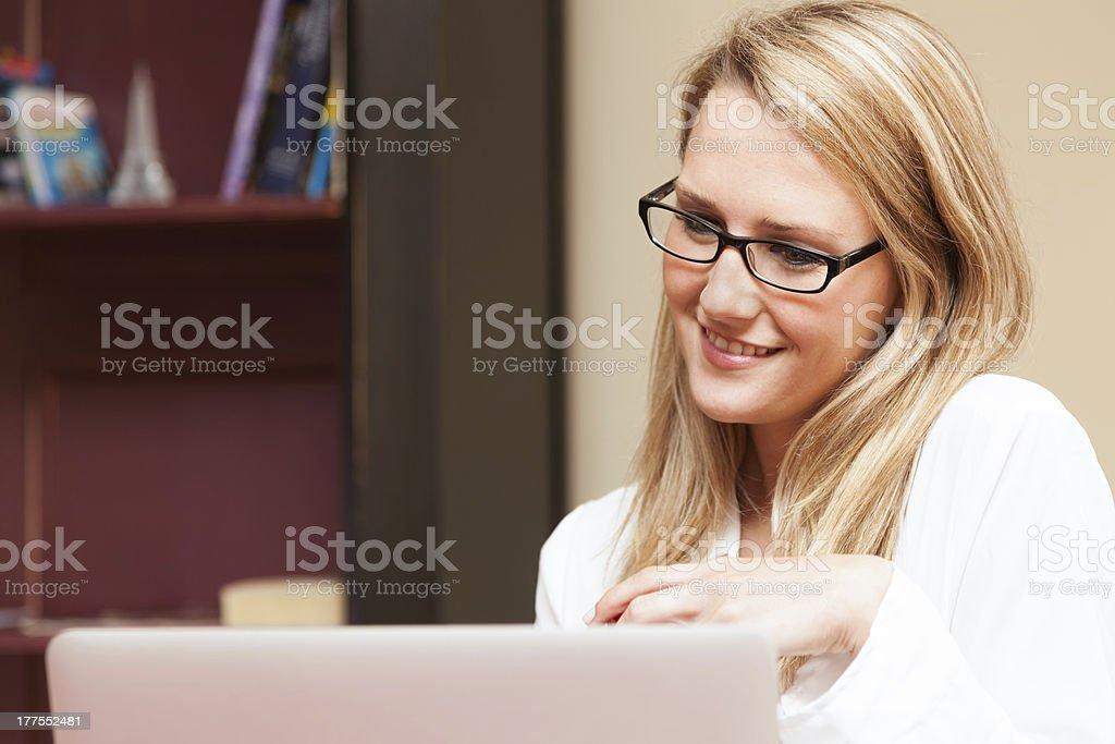 Beautiful Young Woman Smiling at Laptop stock photo