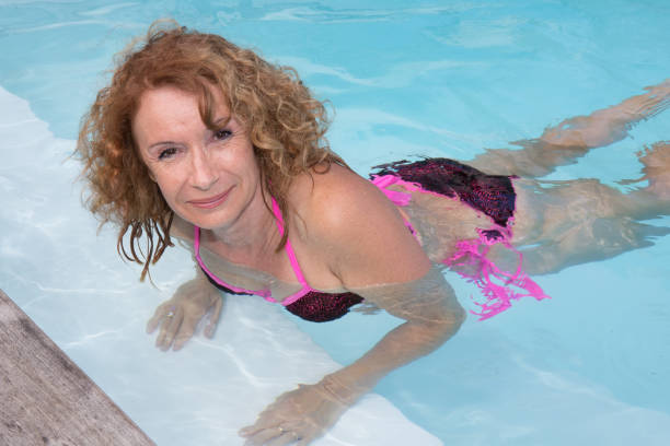 Beautiful young woman smiling in la uxury pool Preety middle aged woman in bikini in pool middle aged women in bikinis stock pictures, royalty-free photos & images