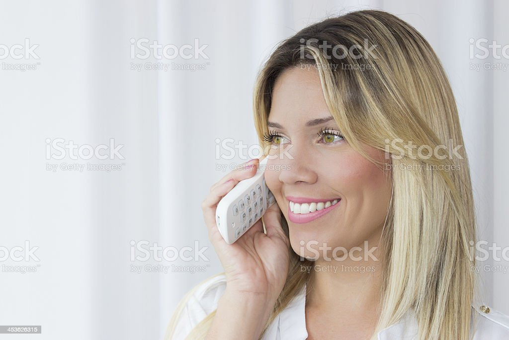 Beautiful young woman, smiling on phone royalty-free stock photo