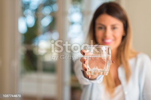 Beautiful young woman smiling while holding a glass of water at home. Lifestyle concept.