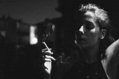 Black and white picture of serious young attractive woman smoking a cigarette outdoor in the night