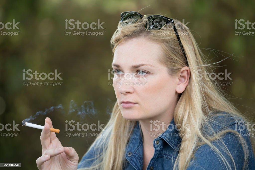 Beautiful Young Woman Smoking a Cigarette stock photo