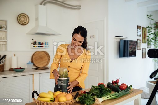 Social media influencer, a happy smiling young woman preparing food using blender and recording a tutorial for her youtube food channel.