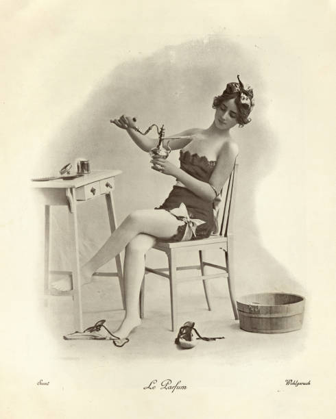 Beautiful young woman spraying on perfume, Victorian vintage photograph stock photo