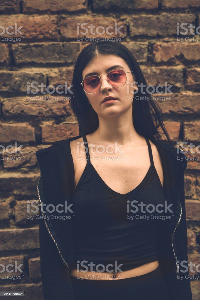 Beautiful young woman standing brick wall in an urban environment royalty-free stock photo