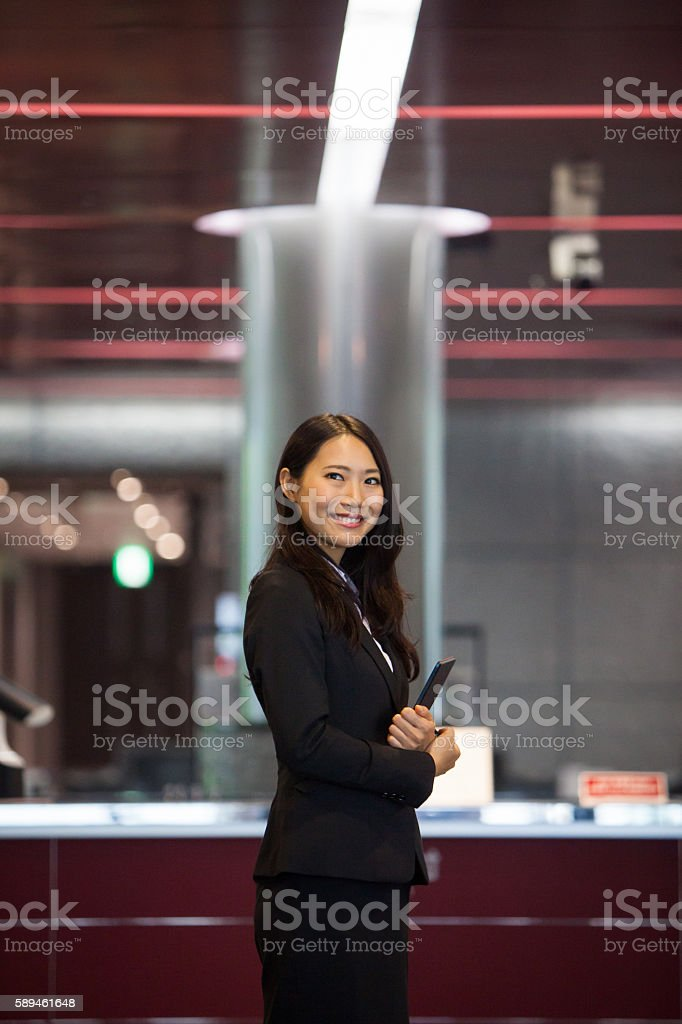 Beautiful young woman standing greeting guests stock photo