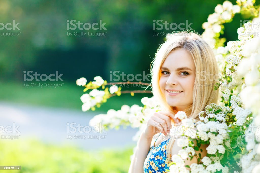 Beautiful young woman standing in a lush white garden royalty-free stock photo