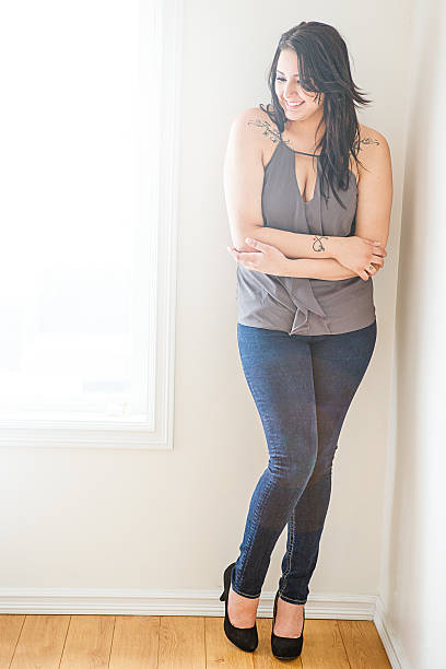 schöne junge frau stehend auf etage - damen jeans übergrößen stock-fotos und bilder