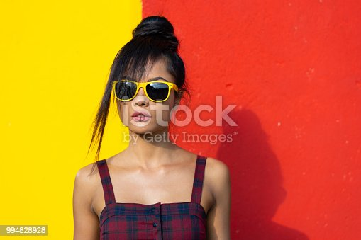 Beautiful young woman posing in front of colored wall.
