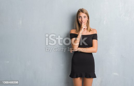 Beautiful young woman standing over grunge grey wall wearing elegant dress asking to be quiet with finger on lips. Silence and secret concept.