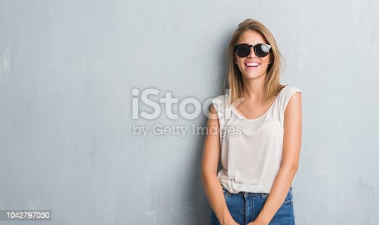 istock Beautiful young woman standing over grunge grey wall wearing fashion sunglasses with a happy face standing and smiling with a confident smile showing teeth 1042797030