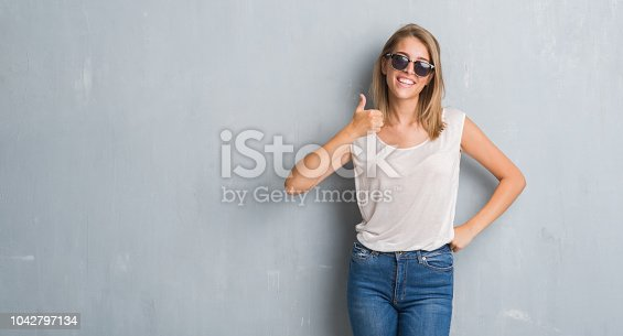 Beautiful young woman standing over grunge grey wall wearing fashion sunglasses happy with big smile doing ok sign, thumb up with fingers, excellent sign
